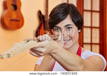 Woman as carpenter controls guitar fingerboard with precision
