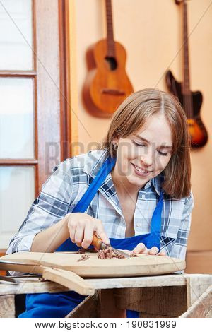 Young woman processing wood in luthier apprenticeship
