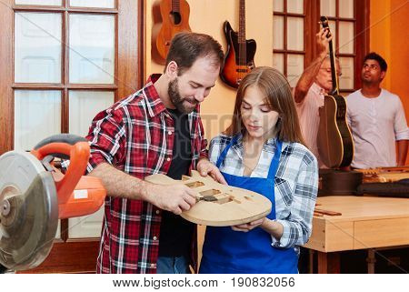 Woodworker shows apprentice guitar building during apprenticeship