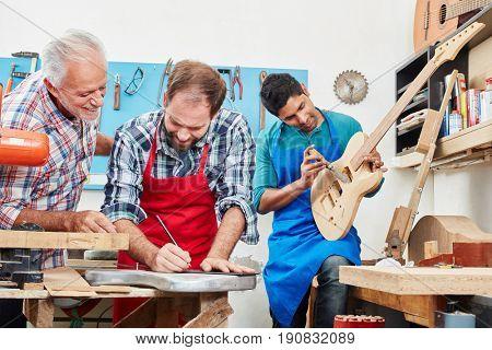 Senior guitar maker controls apprentice's work during test
