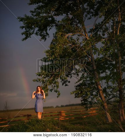 Beautiful woman and rainbow in the sky