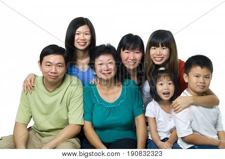 Larger Asian family portrait on white background, three generations.