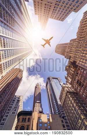 plane flying over highrise office buildings in the sun, Manhattan, New York City