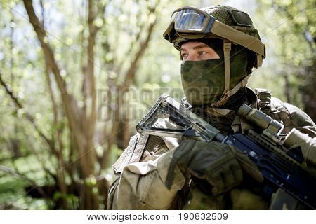 Soldier in goggles looks sideways at forest