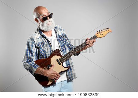 Senior man with guitar on grey wall background