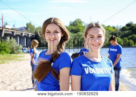 Young girls standing on beach near river. Volunteer concept