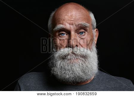 Sad senior man on black background