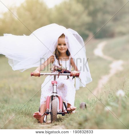 Young bride playing wedding summer outdoor, newlyweds. Little girl in bride white dress and bridal veil posing over fresh greenery on bicycle. Bridal, wedding concept, image toned and noise added.