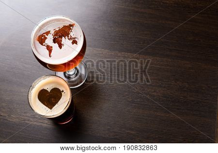 World map and heart silhouettes on foam in beer glass on pub table, view from above. Elements of this image furnished by NASA