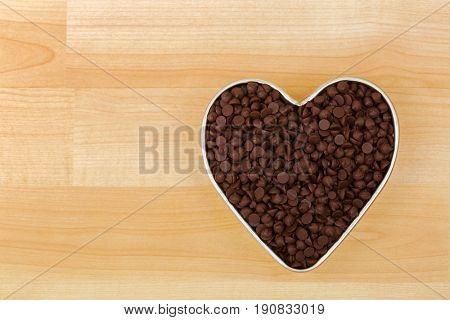 Small chunks of sweetened chocolate chips in heart shaped tin bowl on wooden background with copyspace