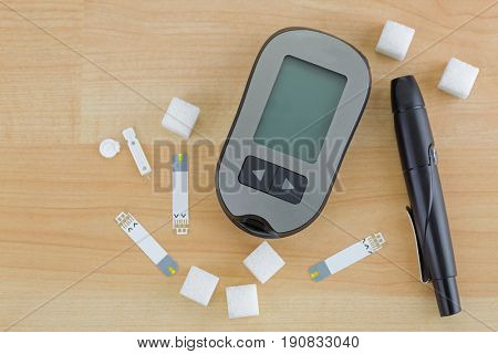 Sugar cubes next to Blood Glucose meter, test strip, lancing pen device on wooden background