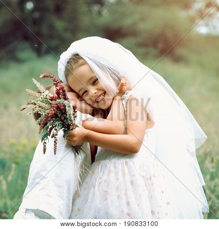 Young bride and groom playing wedding summer outdoor. Children like newlyweds. Little boy groom kissing his young girl in bride white dress and bridal veil. Bridal, wedding concept, image toned.