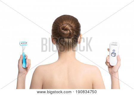 Beautiful young woman with razor and epilator on white background