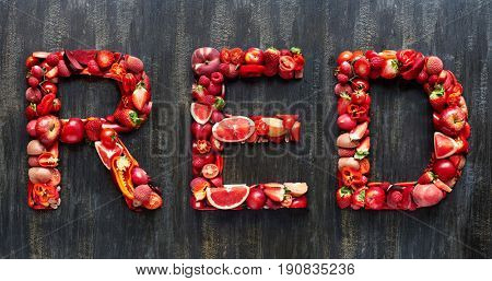 Red spelled with colored fresh produce, part of collection of food words formed with single or multi coloured fruits and vegetables