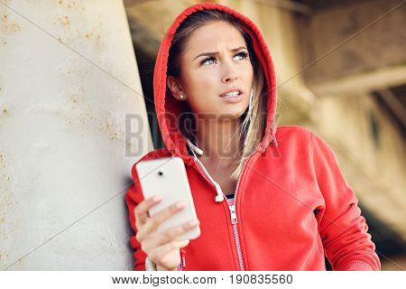 Woman jogging on the beach with smartphone