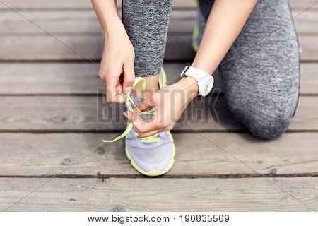 Female athlete runner tying shoelaces