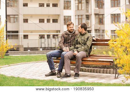 Romantic gay couple sitting on bench