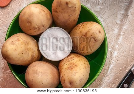 White salt shaker with salt surrounded by raw uncleaned potato tubers
