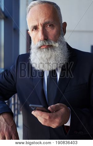 Vertical of man age of 50-60 surfing in mobile phone while leaning on handrail