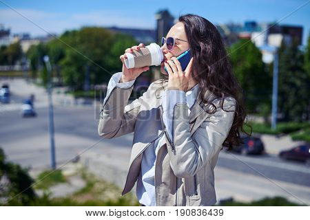 Mid shot of gorgeous lady talking on phone while drinking coffee on top of building