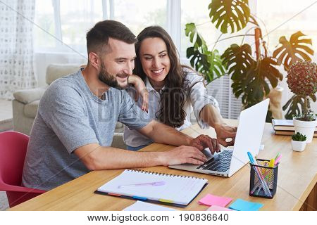 Wide shot of beautiful girl showing something in laptop to boy while sitting in table