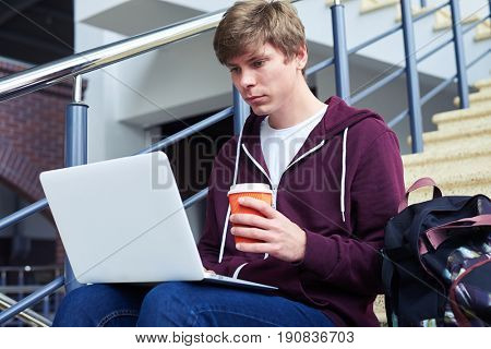 Mid shot of boy with poker face holding cup of coffee while surfing in laptop