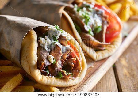 two lamb gyros with feta cheese and tzatziki sauce