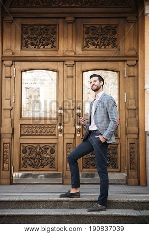 Full length portrait of a smiling handsome man in jacket holding mobile phone while standing infront of a large doorway