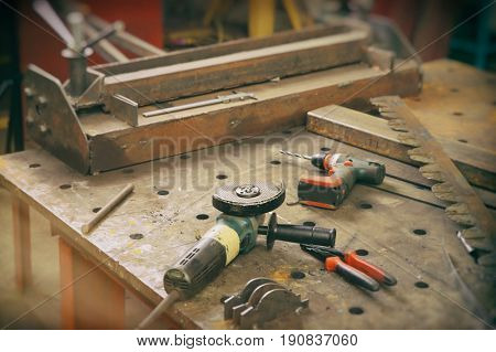 Angle grinder and other tools for metalworking in shop