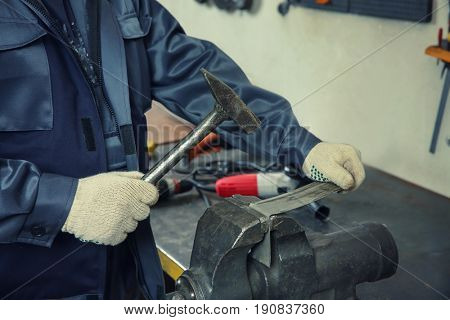 Man using grip and hammer for metalworking in shop