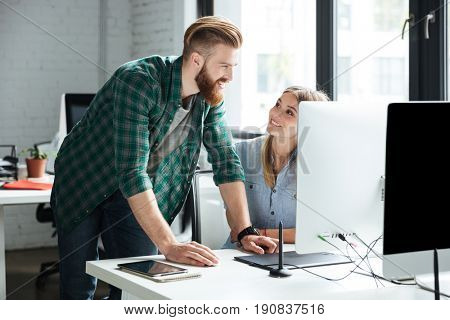 Photo of two young concentrated colleagues work in office using computers. Looking aside.