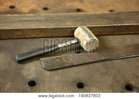 Mallet for metalworking on perforated table in shop
