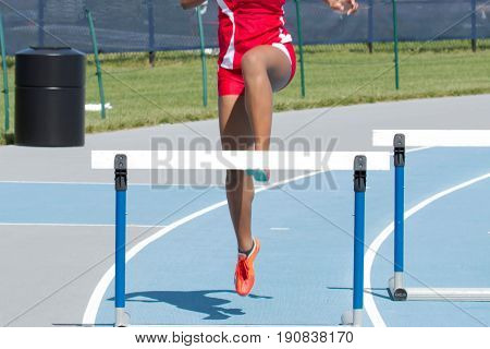 A high school female racing in the 400 meter hurdles on a blue track in lane eight