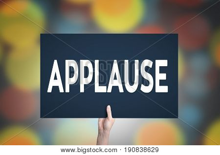 Applause card in hand with bokeh lights background