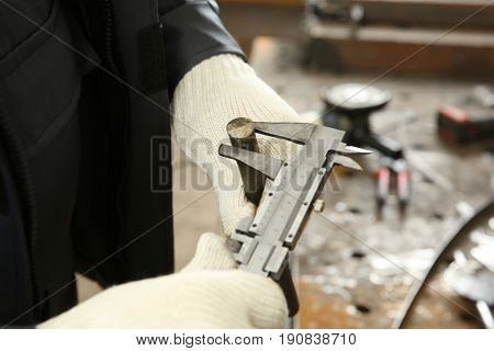 Man using vernier caliper for measuring metal bar in shop