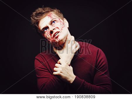 Young man in color contact lenses, with Halloween makeup on black background