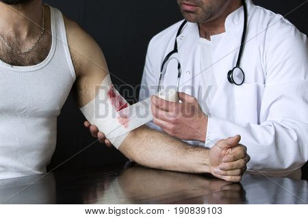 closeup of man with bloody wound getting a bandage from doctor