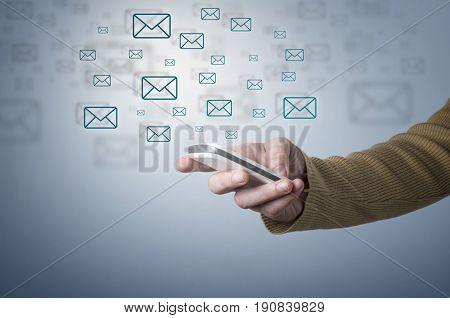 Closeup of male hand using smart phone for reading emails.