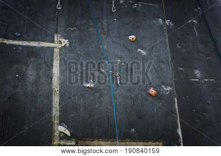 Artificial rock climbing wall. Sport equipment background.