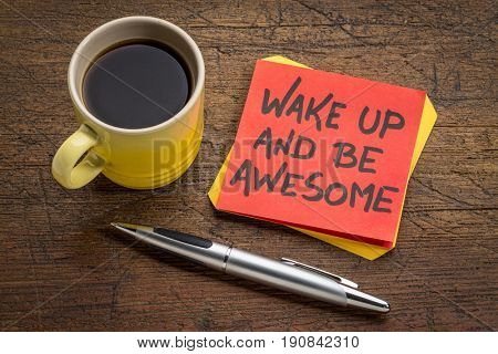 wake up and be awesome - motivational advice on a sticky note with a cup of coffee against rustic wood
