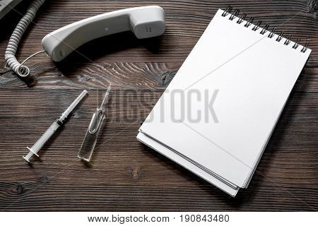 phonendoscope, syringe, ampoule and notebook on dark wooden desk top view call doctor.