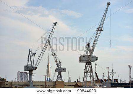 Three grey shipping cranes in a dockyard