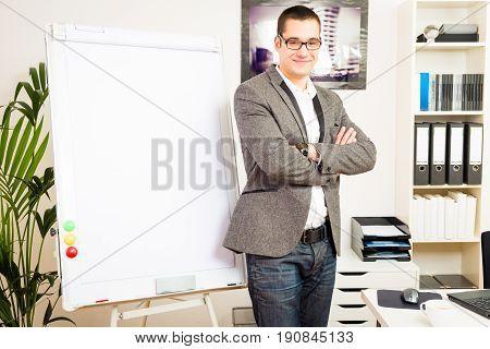 businessman standing next to an empty flipchart