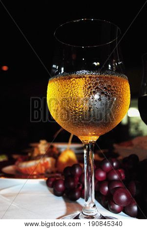 White wine in a wine glass Cold white wine served in a wine glass with moisture in a table setting