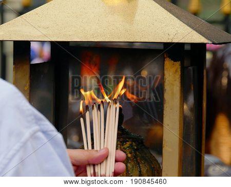 hand holding lighted incense sticks  A man holding up several lighted incense sticks at a shrine in Bangkok, Thailand