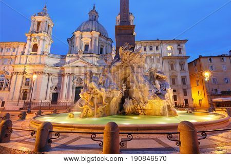 Fountain of the Four Rivers and Sant Agnese Church on the famous Piazza Navona Square during morning blue hour, Rome, Italy.