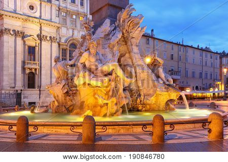 Fountain of the Four Rivers on the famous Piazza Navona Square during morning blue hour, Rome, Italy.