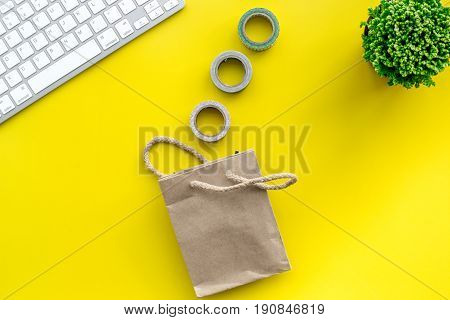 colorful home office desk with plants, paper bag and keyboard on yellow background top view mock up