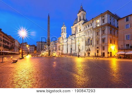 Fountain of the Four Rivers with an Egyptian obelisk and Sant Agnese Church on the famous Piazza Navona Square at night, Rome, Italy.