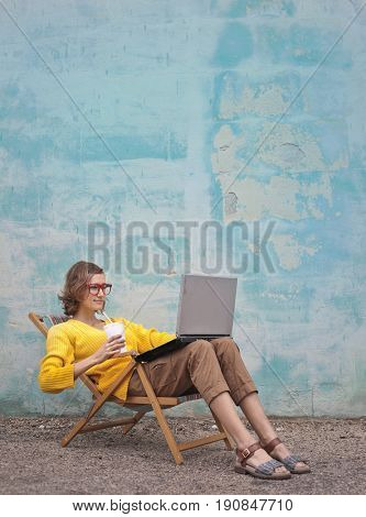 Young woman sitting in a beach chair working at the pc
